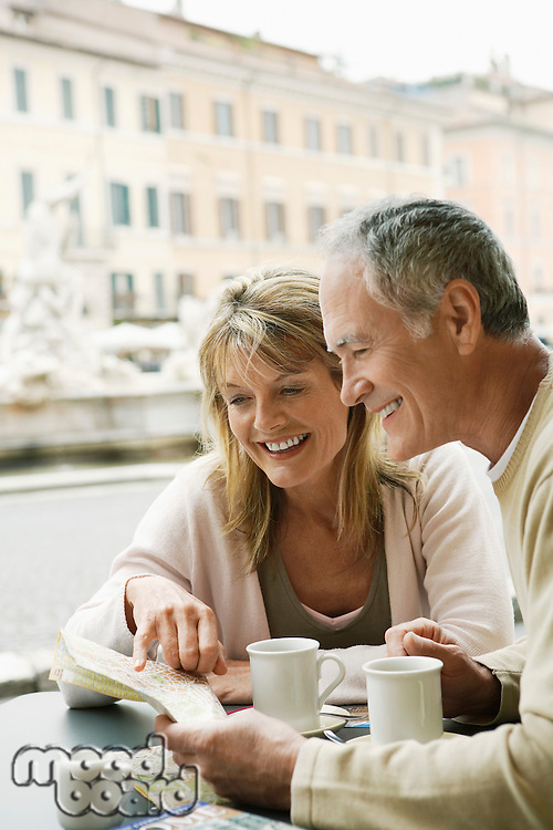 Middle-aged couple at outdoor cafe in Rome looking at map head and shoulders