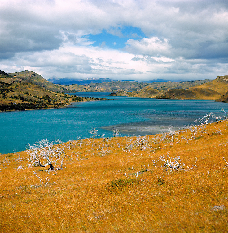 The azure waters of Lake Sarmiento contrast with the ecru colors of the landscape in Torres del Paine NP, Chile.