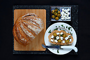 Whole grain loaf on blue grey marble with green olives, feta cheese and fresh parsley, on dark navy table cloth Contact us for Royalty Free options for this image
