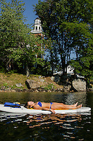 Abbie Roy practicing relaxation during shavasana in Lori Card's SUP Yoga class at EKAL in Meredith Bay Wednesday morning.  (Karen Bobotas/for the Laconia Daily Sun)