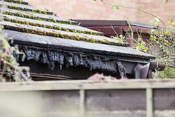 © Licensed to London News Pictures . 23/10/2014 . Penistone , UK . Melted gutters around the house . A fire in a house on Tennyson Close in Penistone near Barnsley has killed a nine year old boy and a 44 year old man and a boy aged 11 is critically ill in hospital . The house ( pictured with solar panels on the roof and smashed windows ) is cordoned off by police . Photo credit : Joel Goodman/LNP