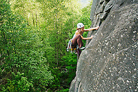 A mid-30s Caucasian woman grips a crag as she ascends a rock face at Mount Index, Washington...Model Release: 20080524_MR_A.jpg