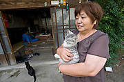 Mieko Takahashi, 63, holds one of her cats as her husband, Takeshi, 67, sits in the living room of there home in Iitate Village, Fukushima Prefecture, Japan on 08 Sept. 2011.  Despite high radiation levels in the village the Takahashis return home every so often to check on there property. Photograph: Robert Gilhooly