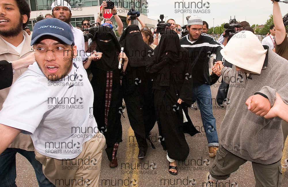 Toronto, Ontario ---06/6/6--- Veiled women escorted by other family members of the accused in a Toronto terrorism plot make their way through a throng of media as they leave at the courthouse in Brampton Ontario, a suburb of Toronto as the suspects appeared in court Tuesday June 6, 2006.