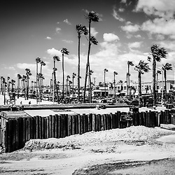 Newport Beach Dory Fishing Fleet Black and White Picture. In the background are businesses along West Oceanfront street between 21st and 22nd Street.  The Dory Fleet is a group of fisherman that operate from the Dory Fish Market by the Newport Pier and sell the catch of the day from the Pacific Ocean. The Dory Fleet is a landmark in Orange County California.