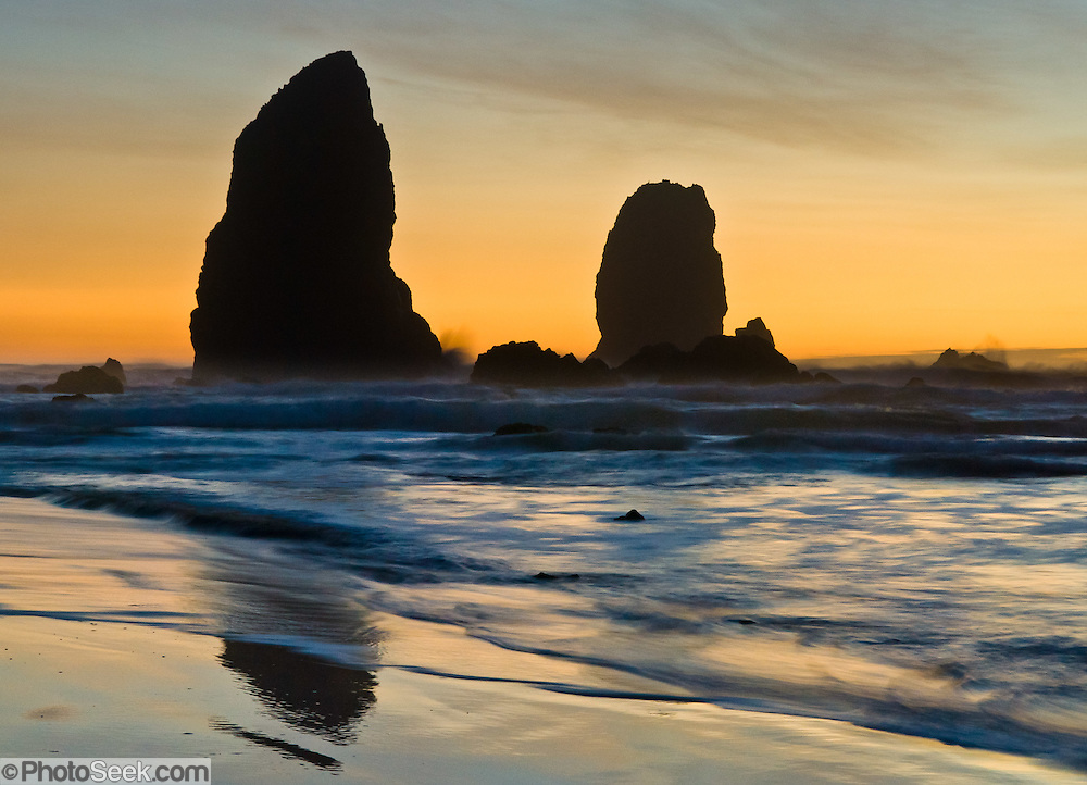 The pounding Pacific Ocean has eroded sea stack rocks from bluffs at Cannon Beach, Oregon, USA. At dusk the sky glows yellow orange. A time exposure blurs the swirling tide.