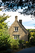 Traditional and typical old stone country cottage by country lane at Swinbrook in the Cotswolds, England, UK