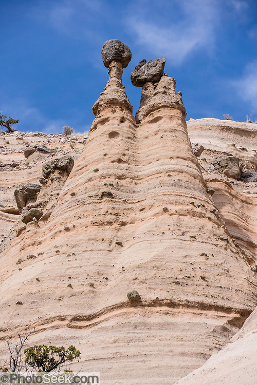 "Cave Loop Trail. See fantastic hoodoos and a great slot canyon in Kasha-Katuwe Tent Rocks National Monument, in New Mexico, USA. Hike the easy Cave Loop Trail plus Slot Canyon Trail side trip (3 miles round trip), 40 miles southwest of Santa Fe, on the Pajarito Plateau. Distinctive cone-shaped caprocks protect soft pumice and tuff beneath. Geologically, the Tent Rocks are made of Peralta Tuff, formed from volcanic ash, pumice, and pyroclastic debris deposited over 1000 feet thick from the Jemez Volcanic Field, 7 million years ago. Kasha-Katuwe means ""white cliffs"" in the Pueblo language Keresan. This panorama was stitched from 3 overlapping photos."