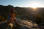 Woman drinking coffee at sunrise deep in the Ansel Adams Wilderness. High Sierra backpacking trip to Garnet Lake and Nydiver Lake in the Ansel Adams Wilderness out of Devil's Postpile national monument 2017.