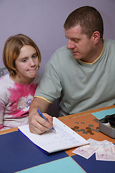Single parent helping young daughter with a shopping list and counting money,