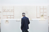 "VENICE, ITALY - 4 JUNE 2016: A visitor looks at the plaster models of Renato Rizzi's ""Orphan Ground"" exhition are here at the 15th Venice Architecture Biennale in Venice, Italy, on June 4th 2016.<br /> <br /> Rizzi says: ""The four projects in section show us, beyond the concrete needs, the internal movements of invisible powers. The 118 models [of this exhibition] hang on the wall to show us how the matter is the aspiration to soul and vice versa."