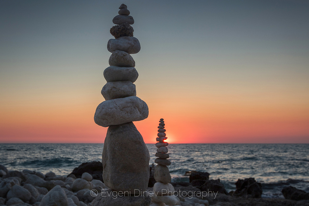 Sunbeam at sunset through a stone pyramid by the sea side