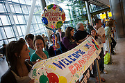"A helium-filled Welcome Home balloon floats in the air and a home-made banner stretches across Heathrow Airport's Terminal 5 arrivals hall. Three families have gathered to meet their respective sons who have been travelling around the world during their university gap year sabbatical trip of a lifetime. With balloon and banner amid the hectic concourse where other relatives greet their loved-ones after months away from home on their adventures. This is a tradition practised across the world's airports where families are separated by the need to travel or work in other countries and the emotion of meeting again after long absences is always hard. From writer Alain de Botton's book project ""A Week at the Airport: A Heathrow Diary"" (2009)."