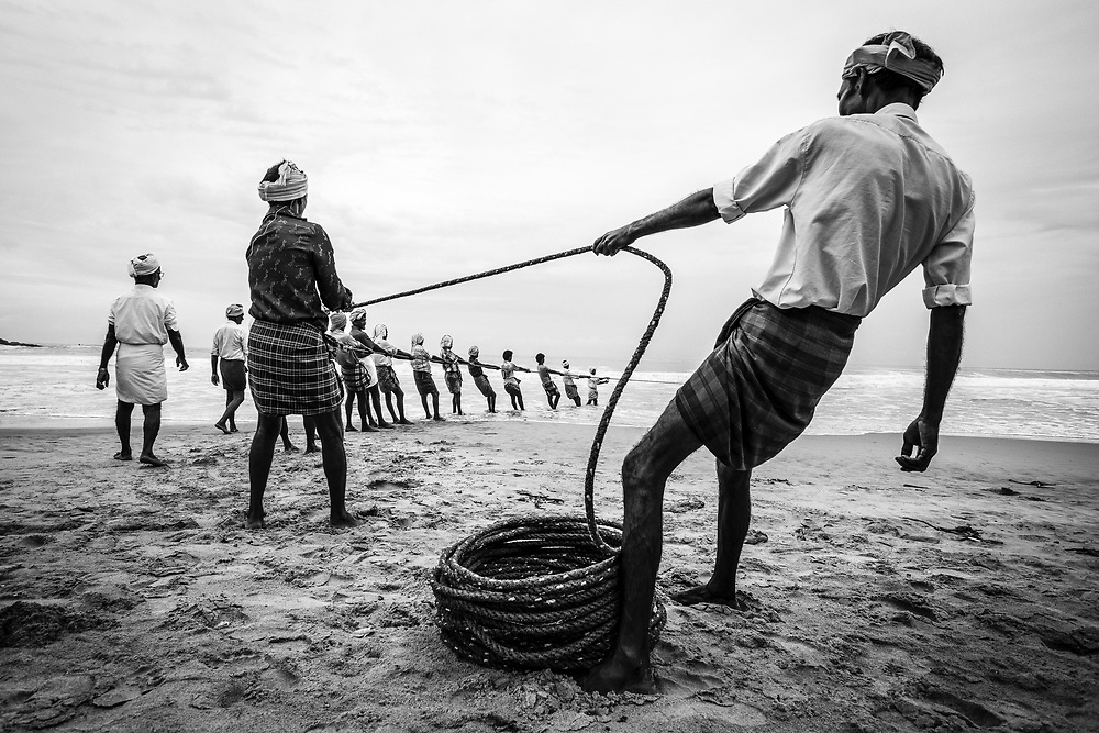 Kerala, India. A fishermen team from Kovalam pulling the fishing nets toward the beach.<br />
