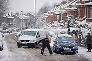 A car owner attempts to shovel his way out of snow on a hill in South London. Bending down to remove the fallen snow from the road, he will again try to get a grip and friction of the slippery surface in order to make it up the gradient in Herne Hill. A van behind is already becoming impatient and is about to get past the stranded car and a passer-by looks on from the pavement, bemused. As the capital's infrastructure ground to a halt, with few trains and no buses for commuters to catch, walking and driving remained the only options.