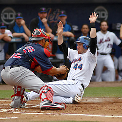 March 6, 2011; Port St. Lucie, FL, USA; New York Mets left fielder Jason Bay (44) slides in safely for a run past Boston Red Sox catcher Luis Exposito (92)during a spring training exhibition game at Digital Domain Park.  Mandatory Credit: Derick E. Hingle