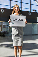 Portrait of attractive woman standing while holding white board with London signage in arrival area at airport