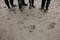 """Guests looking at bear and wolf tracks while on a raft trip down the Tashenshini River. The """"Tat"""" flows out of Yukon, CA, through British Columbia and empties into Glacier Bay National Park in Alaska, US."""