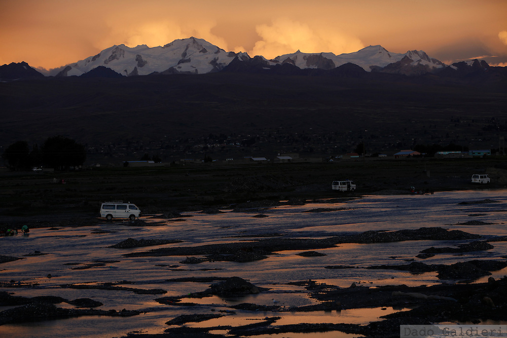 People use the waters of a river in front of the snow capped Illampu mountain to wash clothes and their cars in Achacachi, Thursday, Dec. 10, 2009. While world leaders continuously fail to reach a global agreement to restrict carbon dioxide emissions worldwide,  underdeveloped countries like Bolivia are amongst the most probable to be stroke by climate change effects in the upcoming years.