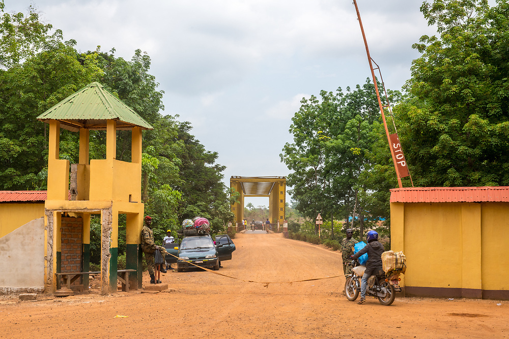 Guards stand at alert to protect border entrance into the Republic of Guinea, as a man on a motorcycle awaits passage out.