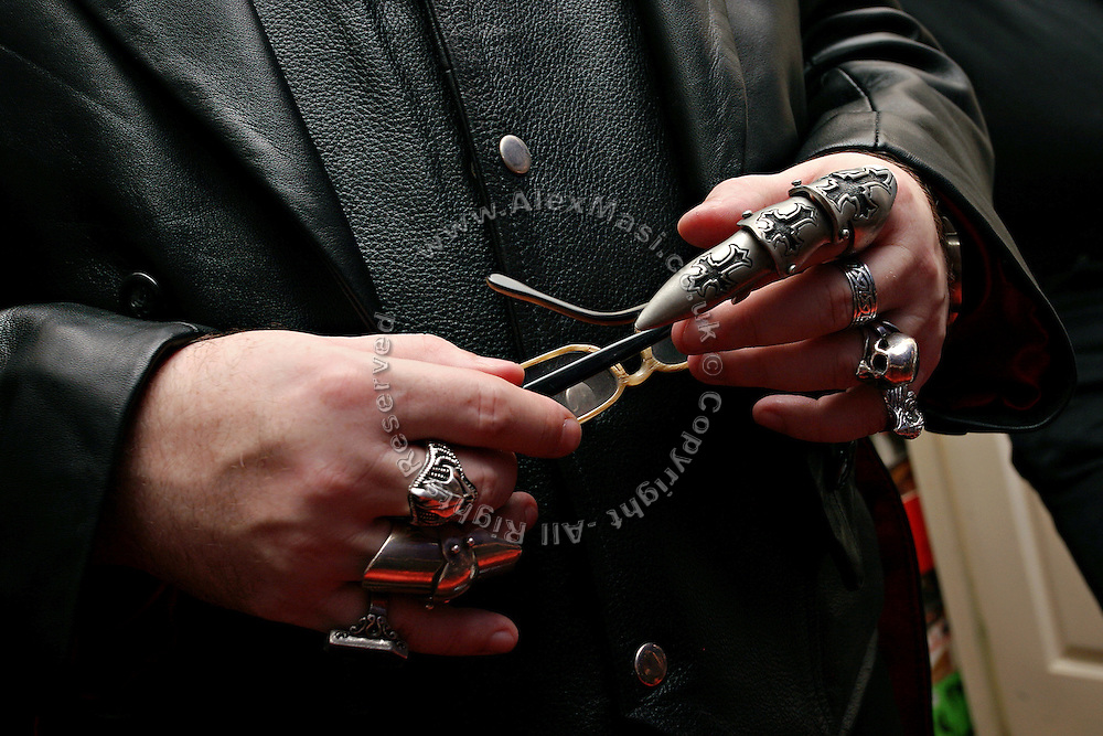 Nick Hook, 42, from London, is holding his glasses while talking to other members in Cecile's living room on Sunday, 15 October, 2006, in Camden Town, London, England. The Vampyre Connexion is the largest and most active of all the vampire groups in the United Kingdom, counting more than 100 members that for years have gathered regularly in London to share their common love for vampires and the Dark side of life. The Connexion raised from the hashes of the Vampyre Society, the first vampire appreciation group in 1995. The group believe in the fantasy of vampires and such creatures and live it to the full. Its  roots are to be found in the legends of Bram Stokerís Dracula. The group prints its own magazine, 'Dark Nights' featuring drawings, poetry, stories, photography and events. All of the members dress very peculiar clothing, and this is a very important part of the life of the group; it is respected with pride, taste and accuracy for the detail. Most like to dress to be elegant in a range of styles from regency to Victorian, some sew their own. In addition members visit art galleries, cemeteries, churches and cathedrals, attend gigs and concerts, and hold their own parties throughout the year, Halloween being the biggest and scariest one. Membership is open to all, the only qualification: being a love of all things Vampyric. **ItalyOut**