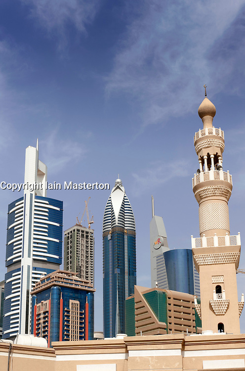 Contrast between Islamic minaret of mosque with new architecture of high rise towers in financial district of Dubai UAE