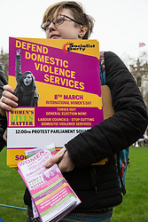 London, UK. 8th March, 2019. Members of the London Region of the Socialist Party protest in Parliament Square on International Women's Day to demand an end to government cuts to domestic violence services.