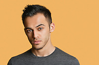 Portrait of a confident young man over colored background