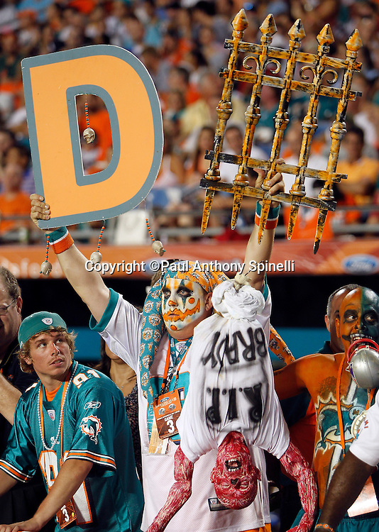 A Miami Dolphins fan with a painted face holds up a defense sign during the NFL week 1 football game against the New England Patriots on Monday, September 12, 2011 in Miami Gardens, Florida. The Patriots won the game 38-24. ©Paul Anthony Spinelli