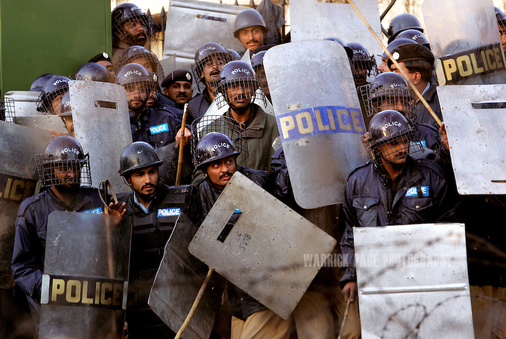 Police take cover from rocks thrown by anti-government demonstrators near the home of the deposed chief justice, Iftikar Chaudry  February 9, 2008 in Islamabad Pakistan. Police used water-canons and tear gas to repel demonstrators as they attempted to march to the home of the former chief justice who remains under house arrest since November last year. Pakistanis will go to the polls later this month after months of political and civil turmoil. (Photo by Warrick Page)