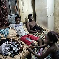 25/07/2014. Conakry. Guinée Conakry. Bidonville de Coronthie. De gauche à droite, Madi, Ibrahima Fall et leur petite soeur Hadja Hawa, enfants de Fatoumata se détendent dans la cuisine. ©Sylvain Cherkaoui/Cosmos pour M le magazine du Monde