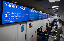 © Licensed to London News Pictures. 23/09/2019. Gatwick, UK. Passenger information screens display a message saying that 'Thomas Cook has ceased trading and all flights are cancelled' at check in desks at Gatwick Airport after the travel firm collapsed overnight. The 178 year old travel operator has gone in to liquidation after rescue talks failed overnight. This will trigger the largest peacetime repatriation as more than 150,000 British holidaymakers will need to be brought home. Photo credit: Peter Macdiarmid/LNP