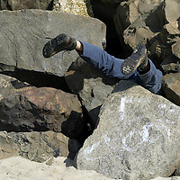 PSUNDAY) Long Branch 4/27/2002  Adam Getzel of Monroe Twp snakes his whole body into the rocks so that all but his legs stick out on the Beach of Brighton Ave during the Clean Ocean Actions beach cleanup day.  This site was sponsored by the surfers alliance.  There was only a dozen or so people there.  Michael J. Treola Staff Photographer.......MJT