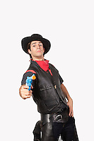 Portrait of young cowboy aiming handgun against gray background