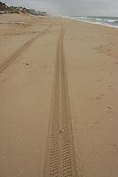 Vehicle tires pneus footprint printed on beach sand.