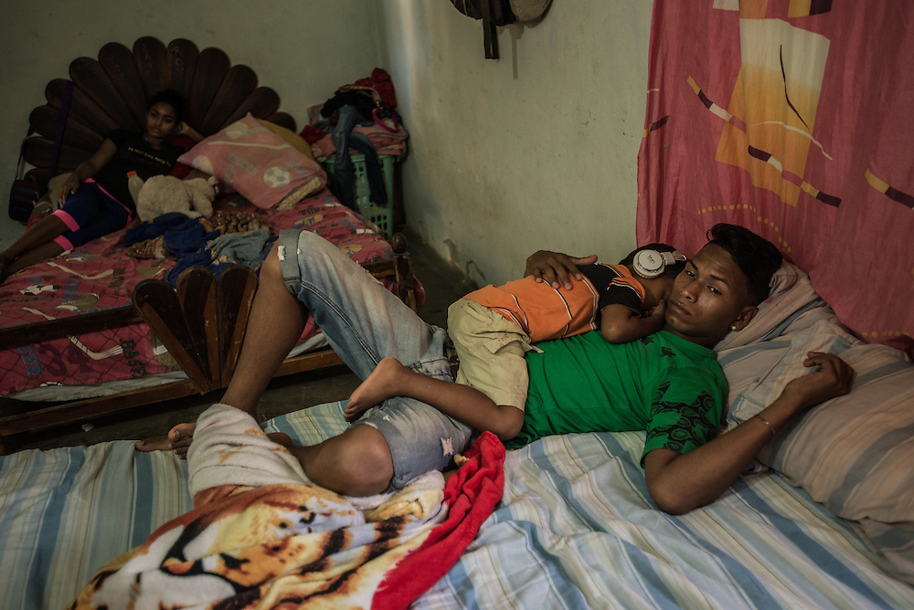 "LA VELA, VENEZUELA - SEPTEMBER 25, 2016: Roger Bello takes care of his nephew, Javier, as he sleeps on his chest. Javier is staying with Roger and Maria, his grandmother, because his mother, Roymar Bello left to work illegally in Aruba after being deported from Curacao. Roger's 19-year-old girlfriend Yaisbel is six months pregnant. He plans to also pay smugglers to take him to Curacao so that he can earn enough money to provide for his future child. Yaisbel said she would stay behind but take a loan from smugglers to pay for Roger's journey, using her mother's house as collateral. Hopefully, she said, her mother would never find out.  ""I am just watching her stomach,"" said Roger Bello. ""Before the child is here, I will be in Curaçao."" PHOTO: Meridith Kohut for The New York Times"