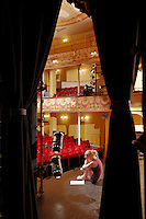 Young woman on stage view through stage curtain
