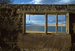 adobe wall and window frame overlooking a lake in Las Vegas, NM