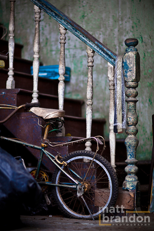 An old staircase with paint peeling provides support for a child's bicycle.