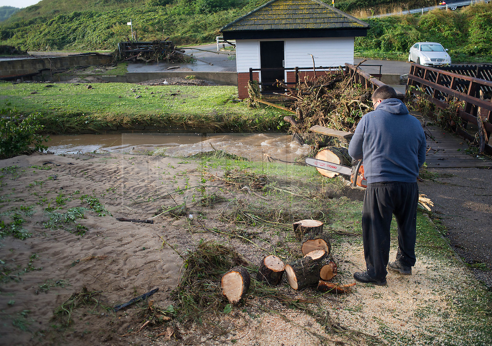© Licensed to London News Pictures. 07/09/2013<br /> <br /> Saltburn, Cleveland, England<br /> <br /> A man begins to chop logs from large trunks washed down following an evening of torrential rainfall that caused flooding and disruption to Saltburn in Cleveland.<br /> <br /> Photo credit : Ian Forsyth/LNP