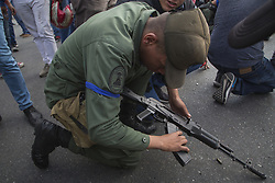 April 30, 2019 - Caracas, Venezuela - Soldier reloads his machine gun. Demonstrators gather near La Carlota air force in Caracas, Venezuela. Through a live broadcast via social media, Venezuelan opposition leader Juan Guaido called for a military uprising against the government of Nicolás Maduro. He declared to be at the air base of La Carlota and was seen surrounded by soldiers and opposition activist Leopoldo Lopez, who was under house arrest. (Credit Image: © Jonathan Lanza/NurPhoto via ZUMA Press)