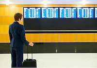 A young businesswoman with her luggage in an airport looking at the departures board.