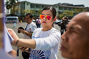 "01 FEBRUARY 2014 - BANGKOK, THAILAND: People look up their names on voter rolls before voting at an open polling place in Bangkok. Thais went to the polls in a ""snap election"" Sunday called in December after Prime Minister Yingluck Shinawatra dissolved the parliament in the face of large anti-government protests in Bangkok. The anti-government opposition, led by the People's Democratic Reform Committee (PDRC), called for a boycott of the election and threatened to disrupt voting. Many polling places in Bangkok were closed by protestors who blocked access to the polls or distribution of ballots. The result of the election are likely to be contested in the Thai Constitutional Court and may be invalidated because there won't be quorum in the Thai parliament.    PHOTO BY JACK KURTZ"