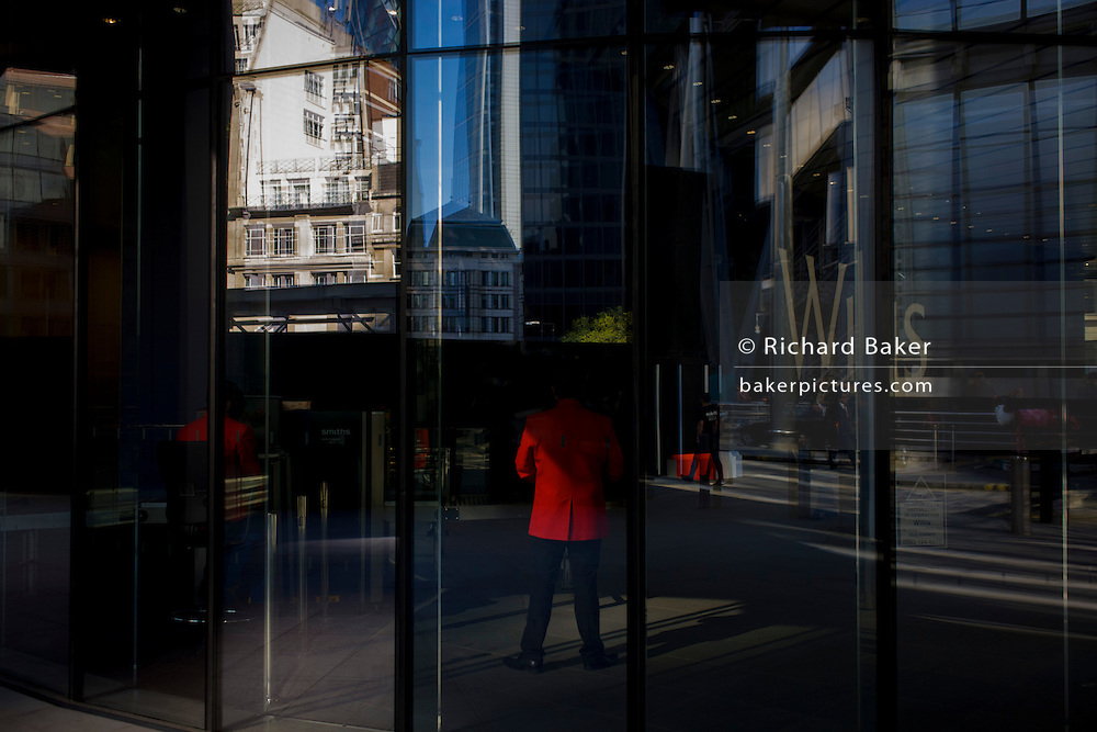 Red jacket security staff stand in the foyer of a large City of London financial institution in Lime Street.