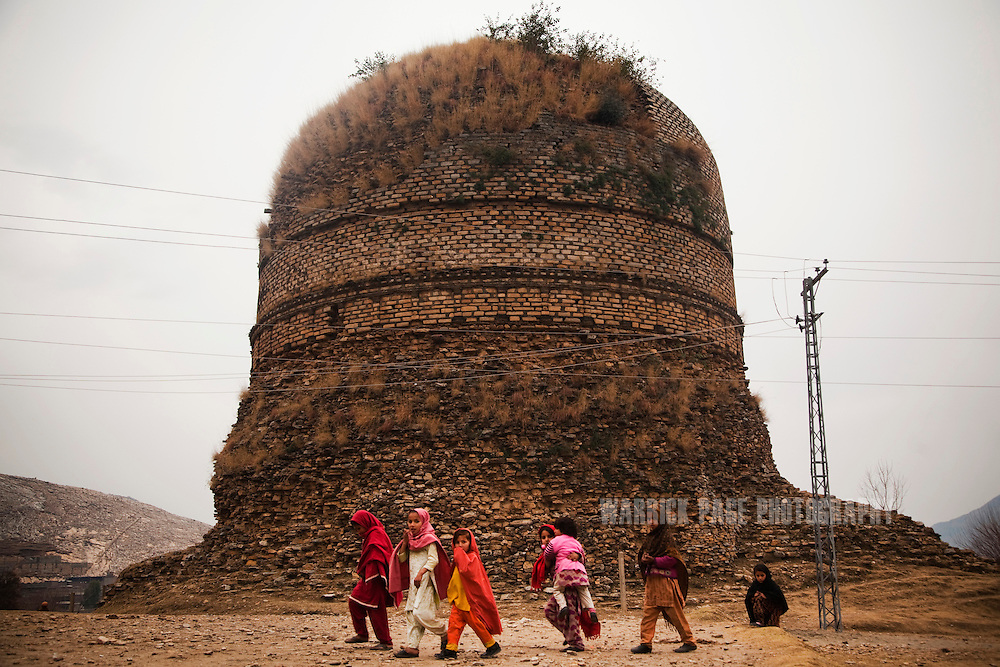 Village children walk past the Shingardar Stupa in the Swat Valley, on February 11, 2011, in Gumbatuna, Pakistan. The Kingdom of Gandhara lasted from early 1st millennium BC to the 11th century AD, and was located in northern Pakistan and eastern Afghanistan. (Photo by Warrick Page)