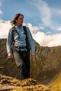 A woman walking at Scales Tarn and Sharp Edge, Blencathra, Lake District, Cumbria, England, UK