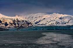 A blue tidewater glacier in front of snow covered mountains