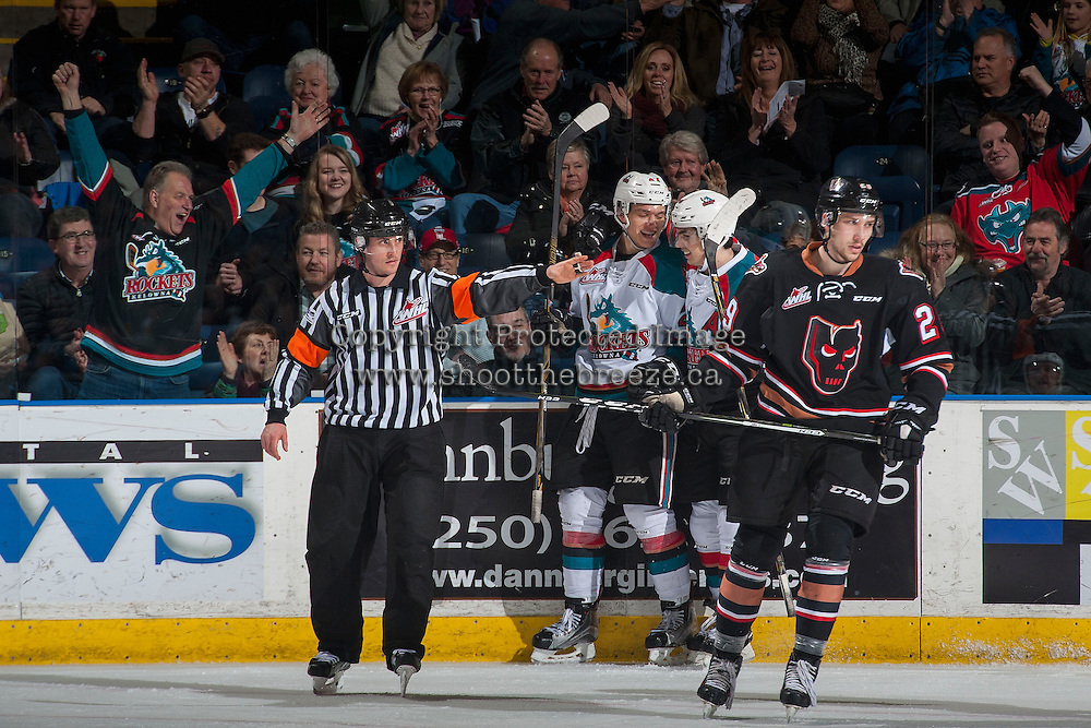 KELOWNA, CANADA - FEBRUARY 1: Referee Bryan Bourdon makes a goal signal as Calvin Thurkauf #27 and Nick Merkley #10 of the Kelowna Rockets celebrate at the boards behind Brady Reagan #29 of the Calgary Hitmen on February 1, 2017 at Prospera Place in Kelowna, British Columbia, Canada.  (Photo by Marissa Baecker/Shoot the Breeze)  *** Local Caption ***