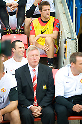 WIGAN, ENGLAND - Saturday, August 22, 2009: Manchester United's substitute Michael Owen sits on the bench behind manager Alex Ferguson before the Premiership match against Wigan Athletic at the DW Stadium. (Photo by David Rawcliffe/Propaganda)