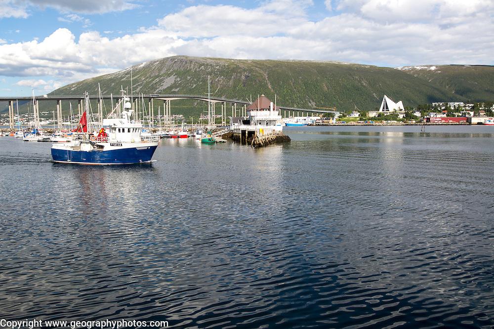 Boats at moorings and fishing boat and bridge at Tromso, Norway